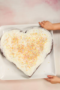 Frosted heart-shaped cake with sprinkles