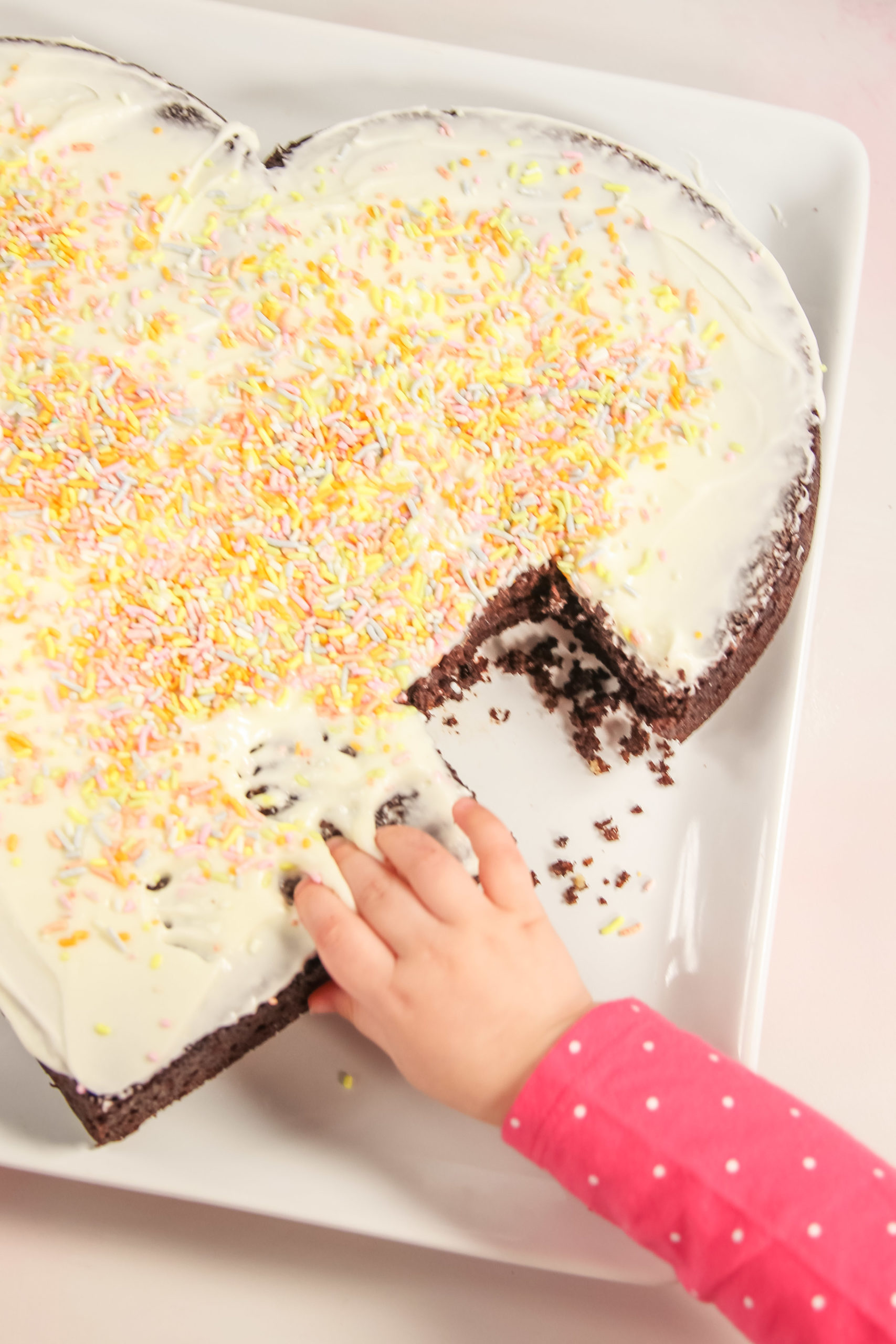 Kid grabbing a piece of heart shaped cake