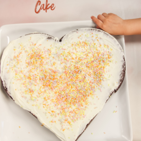 Heart shaped cake on white plate with kids hand