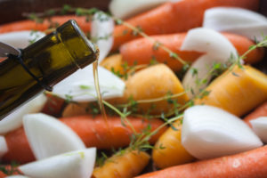 pour olive oil on carrot and onions for roasting chicken