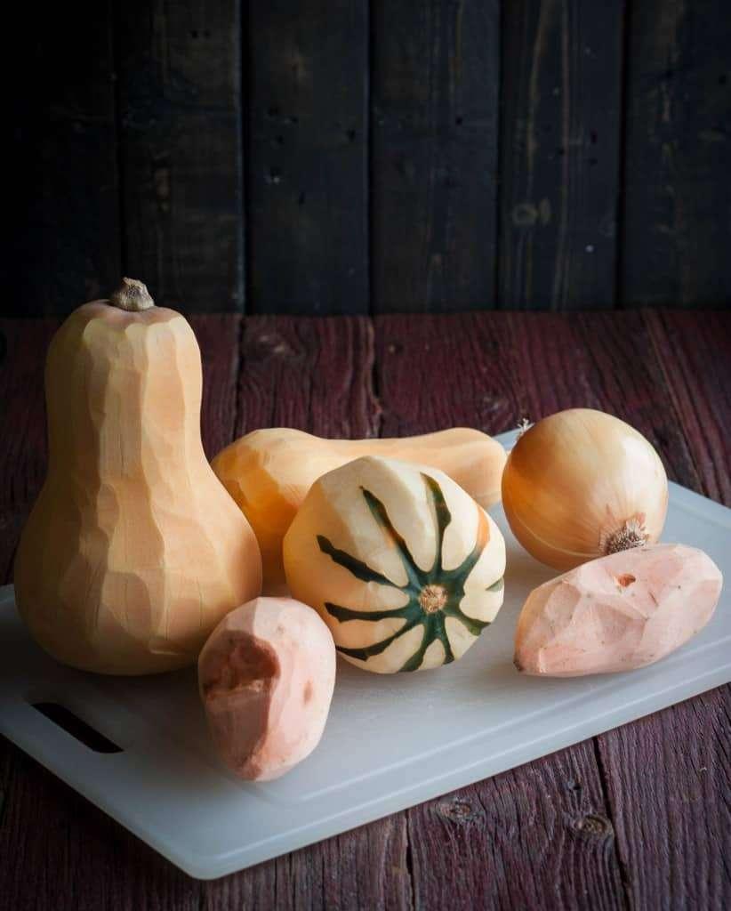 Peeled butternut squash acorn squash sweet potatoes and an onion