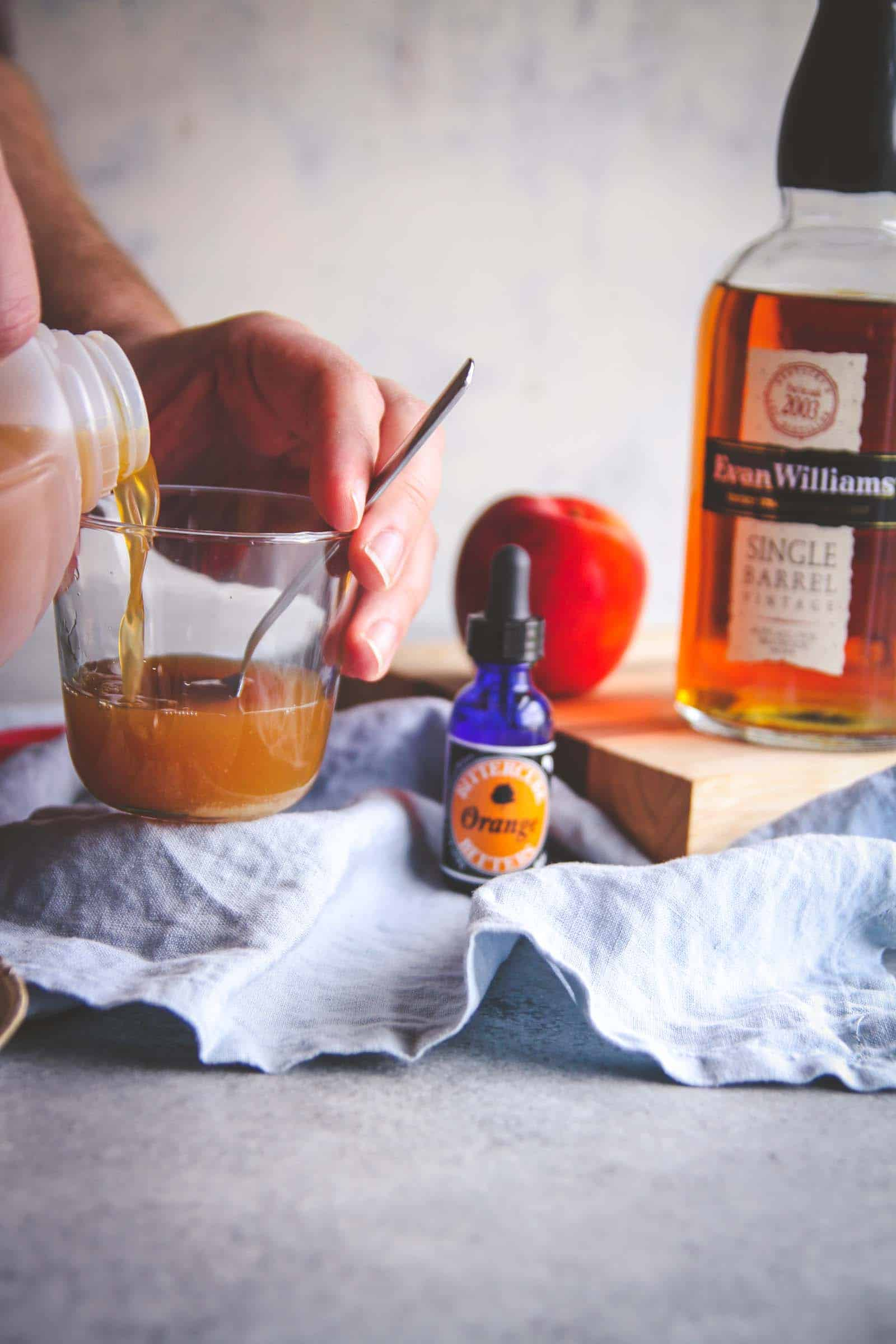 Making an old fashioned cocktail with apple cider