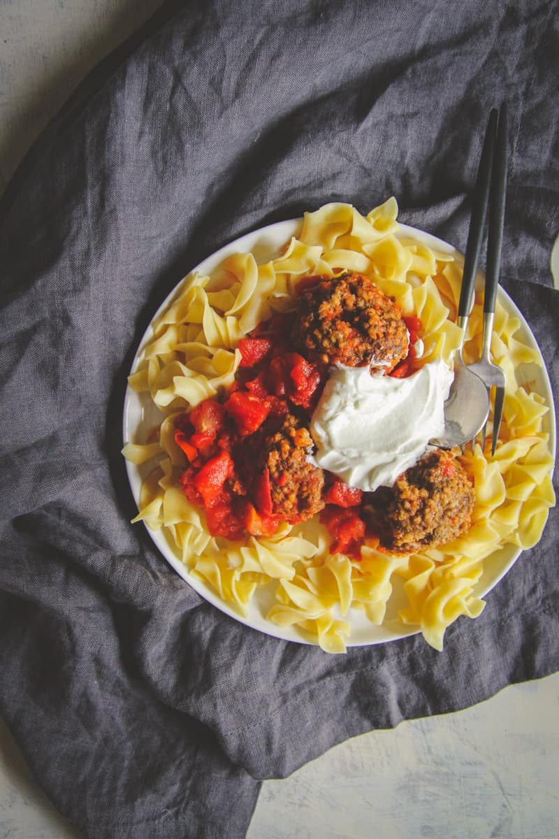 The best ever amb meatballs with a homemade yogurt sauce over egg noodles