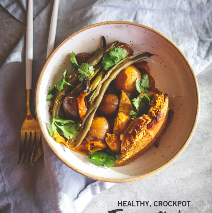 Turmeric chicken & potatoes dinner in a white bowl with silverware