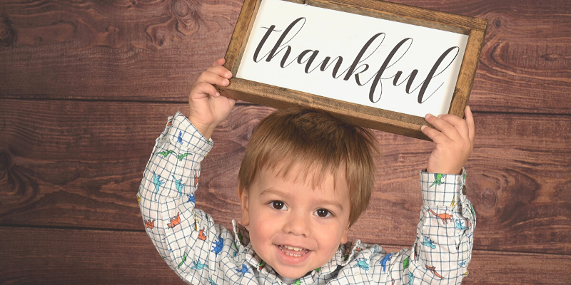 My son holding a thankful sign