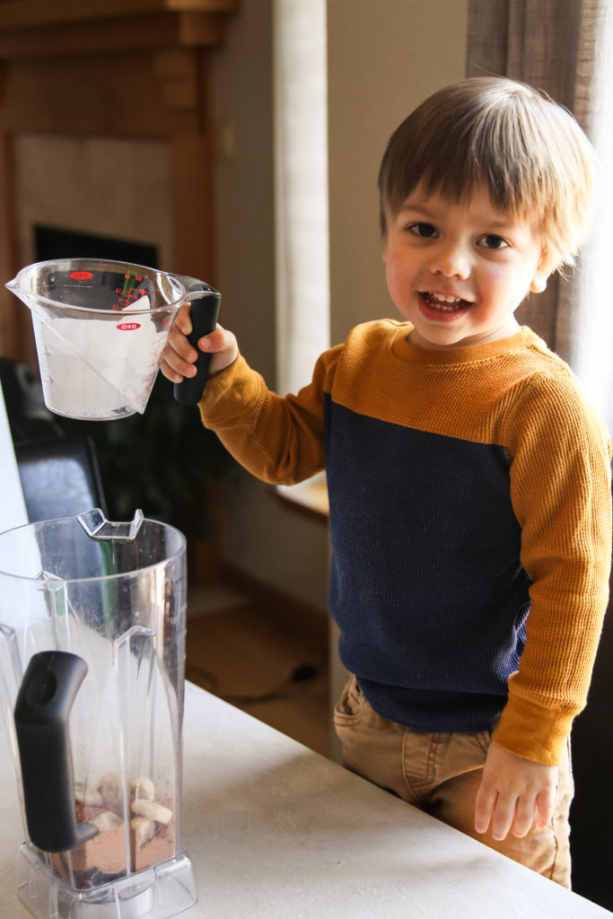 Toddler helping make smoothies