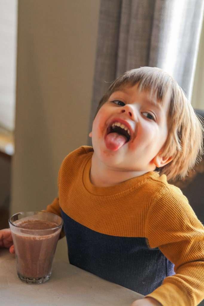 Toddler being goofy with milkshake