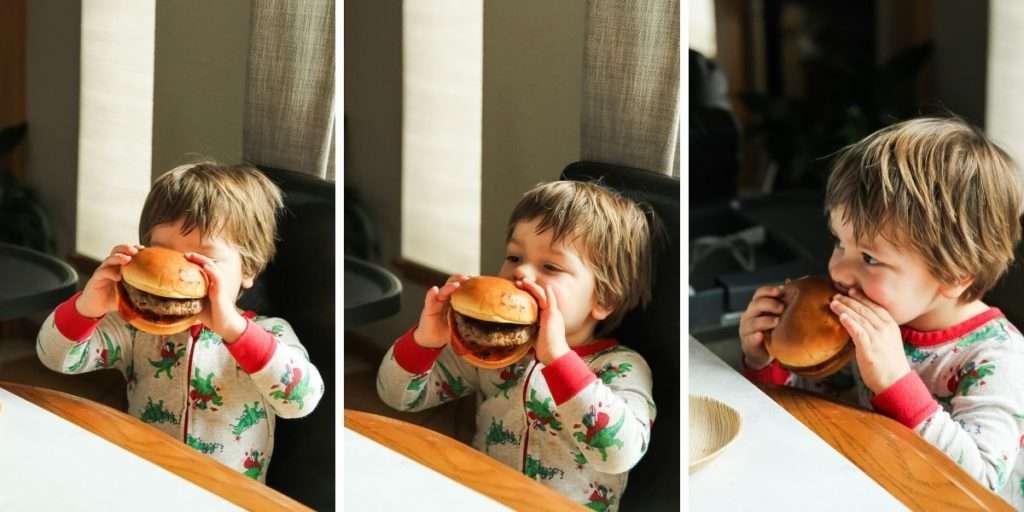 Toddler eating a big burger