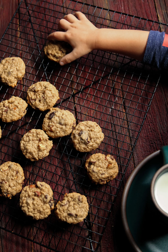 Grabbing one of the best oatmeal chocolate chip cookies on cooling rack