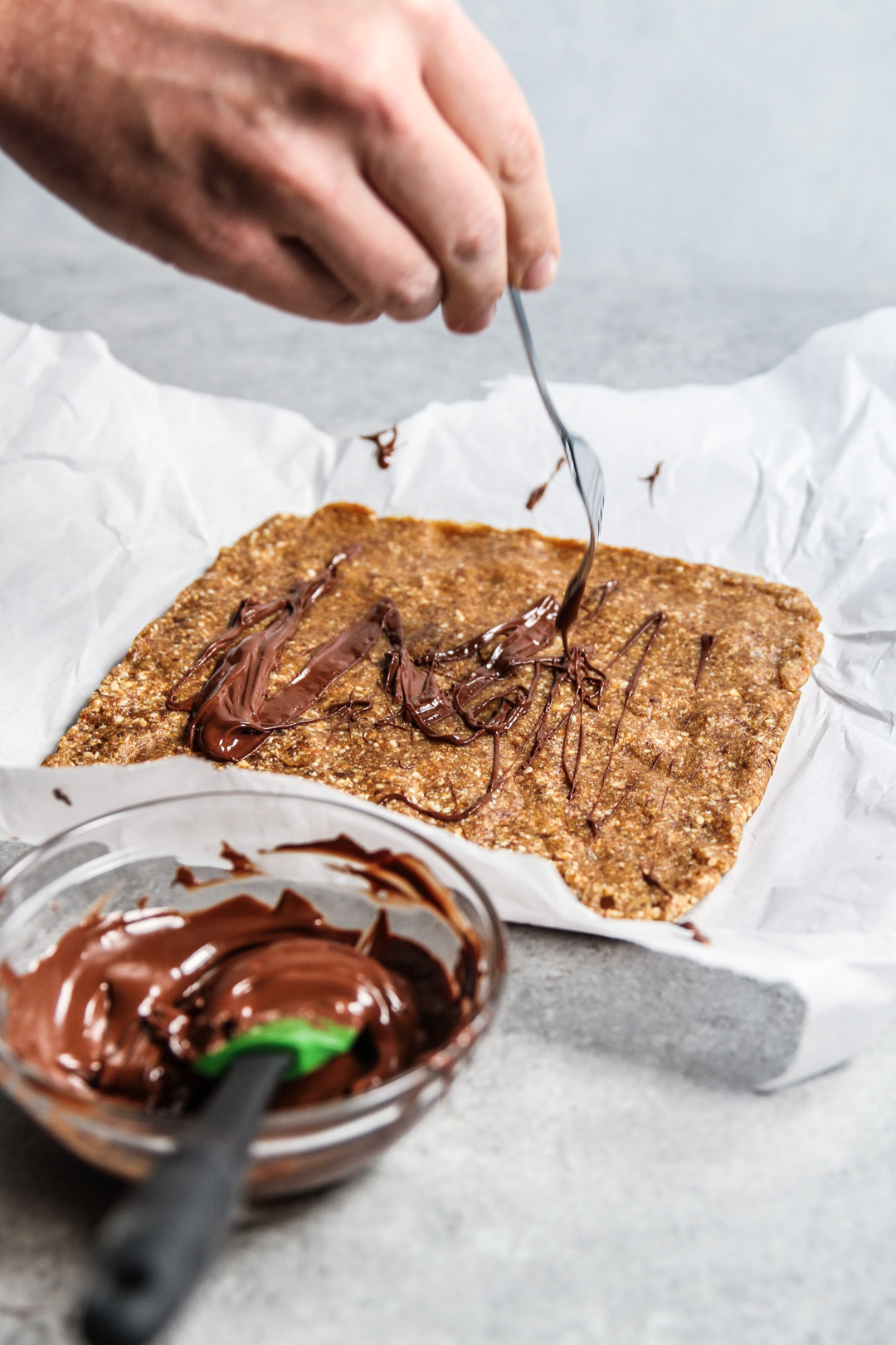 Drizzling chocolate on the 3 ingredient cashew snack bars