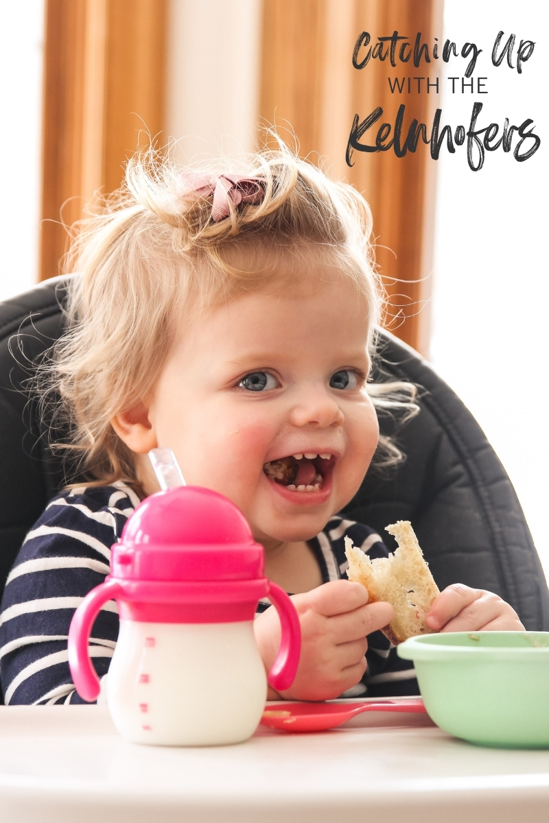 Baby in high chair with sippy cup and bowl