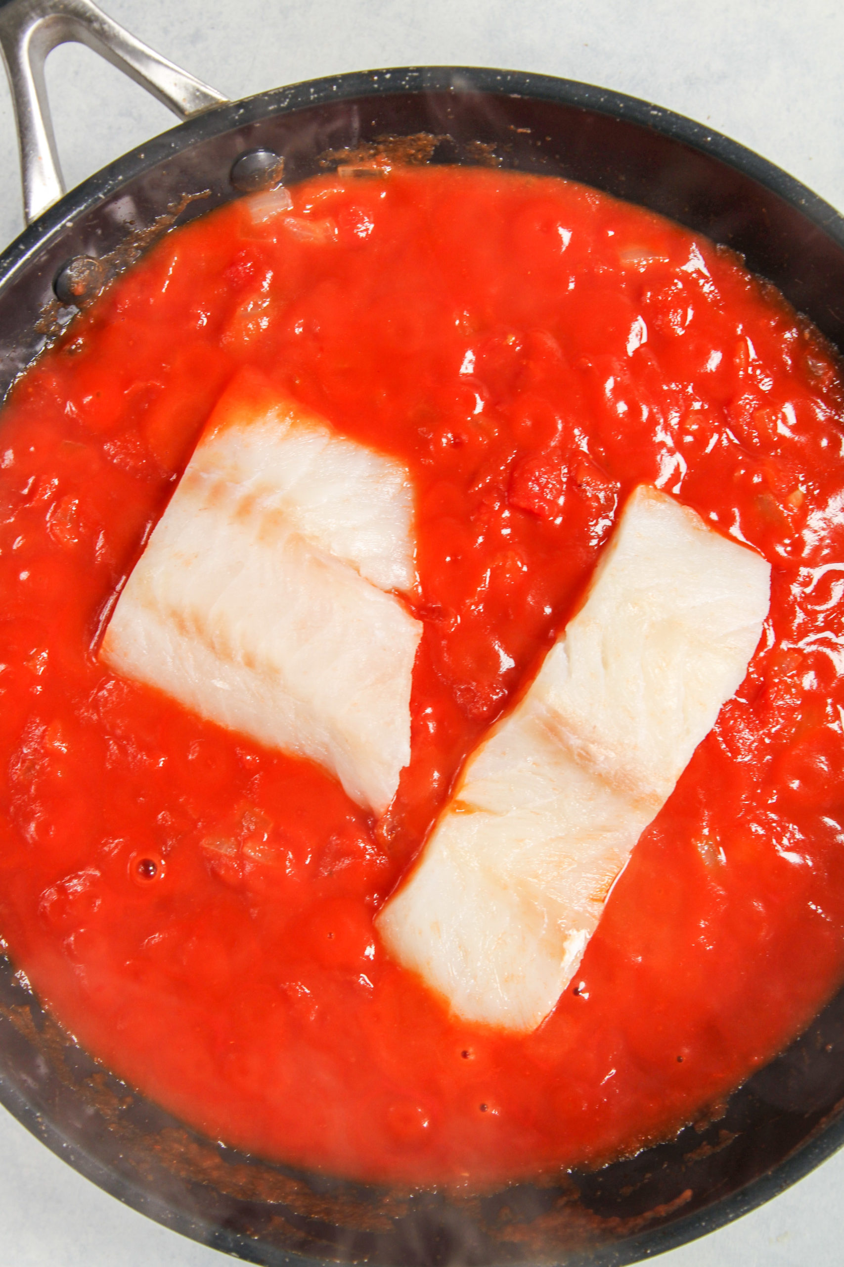 Fish resting in tomato sauce