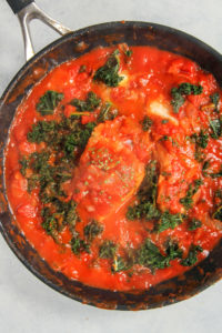Kale and fish in a tomato butter sauce in a large saucepan