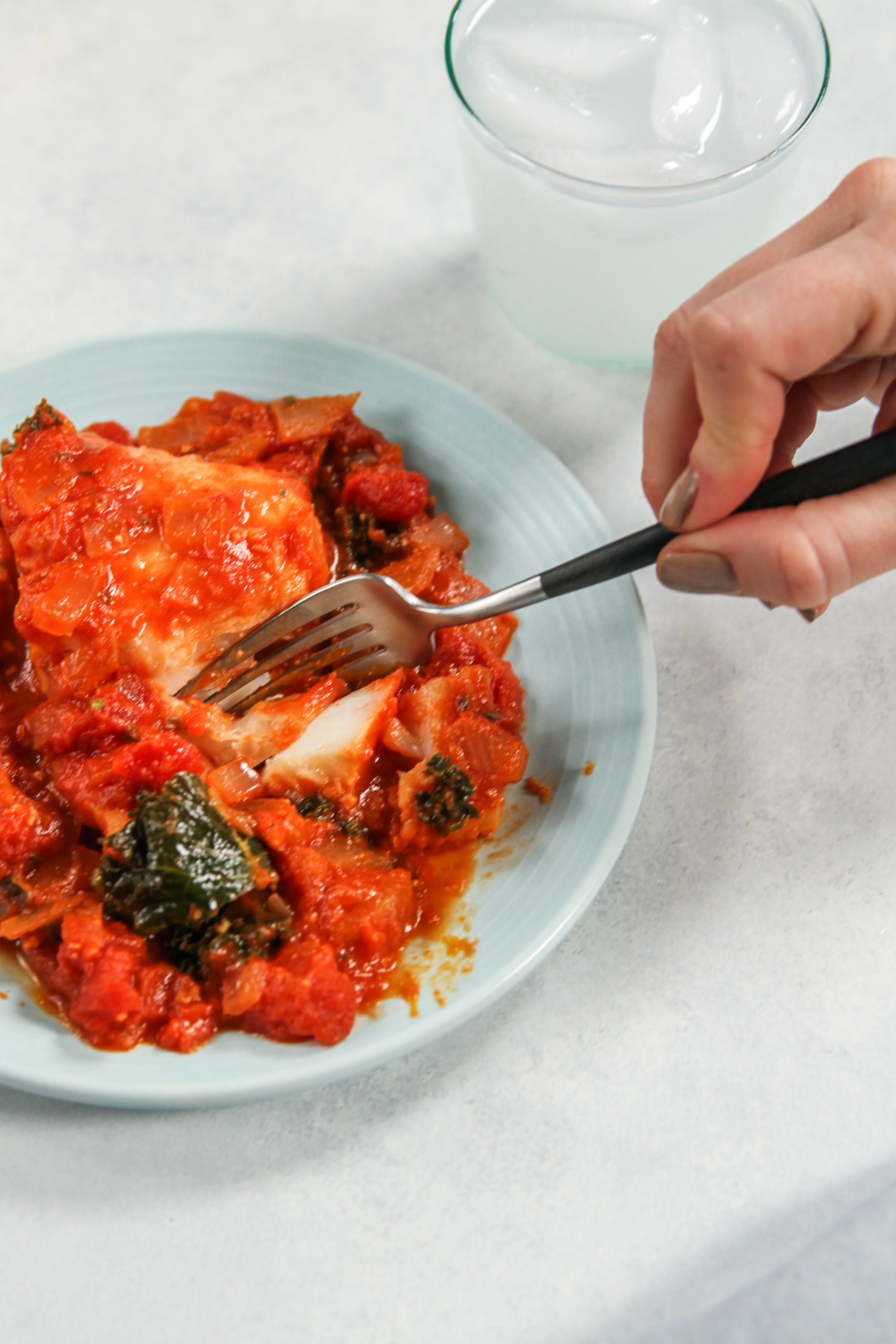 Taking a bite of white fish in tomato sauce